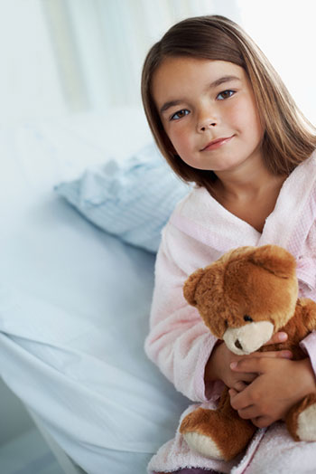 Little girl in pajamas holding a teddy bear