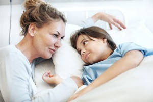Child laying in bed and smiling at mom